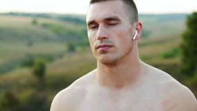Portrait of muscular strong man after training looking at camera, with wireless headphones and bare torso outdoors at. Sunrise, sport and motivation concept stock video footage