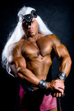 Portrait of a muscular warrior with a sword and a long white hai Royalty Free Stock Photo