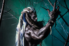 Portrait muscular werewolf with dreadlocks among the branches of Stock Image