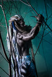 Portrait muscular werewolf with dreadlocks among the branches of Stock Images