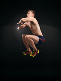 Portrait of muscular young man jumping on black background Stock Photos