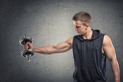 Portrait of muscular young man lifting a dumbbell for training his biceps Royalty Free Stock Photography
