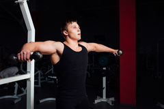 Portrait of a muscular young man lifting weights on gym. Background Stock Images