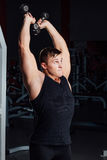 Portrait of a muscular young man lifting weights on gym background. hard training,. Emotions Stock Photo
