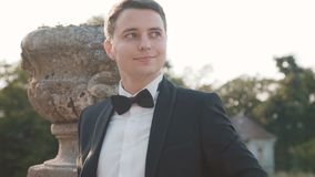 Portrait of mused happy groom smiles and looks aside at castle stock video footage