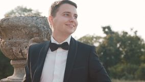 Portrait of mused happy groom smiles and looks aside at castle stock footage