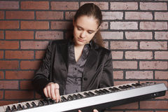 Portrait of musician. With midi key board near brick wall Stock Photography