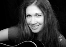 Portrait of a Musician. A smiling girl sits in front of a black background and plays guitar Royalty Free Stock Photography