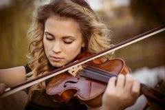 Portrait of musician. Young woman playing the violin at park. Shallow depth of field Royalty Free Stock Photography