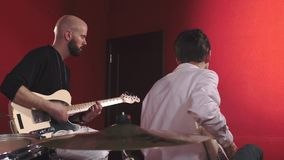 Portrait of musicians on red background. Portrait of musicians. Two guitarists stock video