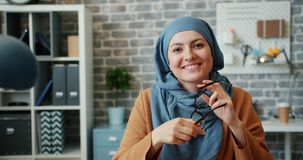 Portrait of Muslim businesswoman in hijab holding glasses sitting in office. Portrait of attractive young Muslim businesswoman in hijab holding glasses sitting stock footage