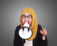 Muslim Businesswoman Yelling Motivating with Megaphone. Portrait of muslim businesswoman leader manager wearing hijab shouting yelling motivating with megaphone Royalty Free Stock Images