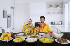 Muslim family having dinner in the kitchen. Portrait of Muslim family looking at the camera while having dinner together in the kitchen royalty free stock images