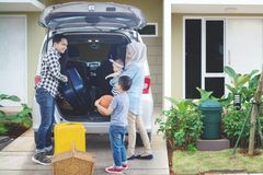 Muslim family preparing for vacation. Portrait of Muslim family looks happy while preparing suitcase into a car for holiday. Shot in the house garage Royalty Free Stock Photo