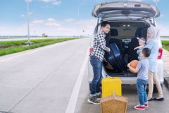 Muslim family ready for road trip. Portrait of Muslim family preparing suitcase into a car for a road trip. Shot on the roadside Stock Photography