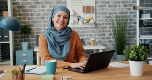 Portrait of Muslim girl in hijab smiling looking at camera in office at desk. Portrait of beautiful Muslim girl in hijab smiling looking at camera in office at stock video