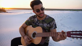 Portrait of Muslim guy who learns to play guitar and sits amidst endless desert at sunset in open air on summer evening. Arabian young man self-taught musician stock video footage