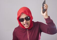 Disappointed Angry Muslim Lady Throwing Her Phone. Portrait of muslim lady wearing black sunglasses in red suit and hijab throwing her phone, mad screaming angry stock photo