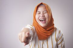 Muslim Lady laughing Hard Bully Expression and Pointing Forward. Portrait of muslim lady wearing hijab laughing hard and pointing forward, bully expression royalty free stock images