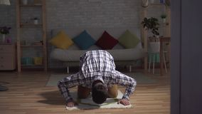 Portrait muslim man sits in a prayer position, raising her hands and praying. In the living room stock video