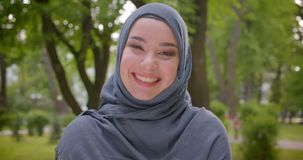 Portrait of muslim woman in hijab with bright make up smiles sincerely and delightfully into camera in the park. stock video footage