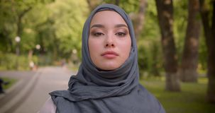 Portrait of muslim woman in hijab with bright make up watching intently into camera walking in the park. stock footage