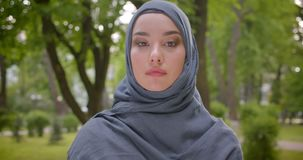 Portrait of muslim woman in hijab watching arrogantly into camera walking in the park. stock video footage