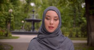 Portrait of muslim woman in hijab watching seriously into camera standing in front of the fountain. stock video