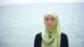 Portrait of a Muslim woman standing near the sea and looking thoughtfully stock video