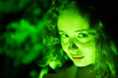 Portrait of a mysterious beautiful woman in green lighting. royalty free stock images
