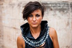 Portrait of a mysterious brunette woman with light eyes and medieval-style leather clothing. In outdoors stock photos