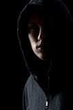 Portrait of mysterious man in the dark. Portrait of mysterious man in hoodie in the dark, dangerous criminal scarcely visible in the dusk Stock Photo