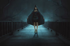 Portrait of mysterious witch with black hooded standing Stock Photo
