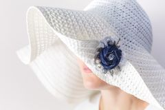 Portrait of a mysterious woman in a white hat with a brooch made of denim handmade Royalty Free Stock Photos