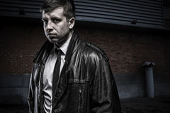 Portrait of mysterious young agent man. Portrait of suspicious young dangerous business man wearing leather coat, looking mysteriously straight to the camera royalty free stock photo