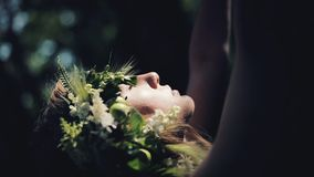 Portrait of mystical girl in the woods hold a ritual. She dressed in long dresses with wreath on the head. Witches