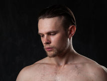 Portrait of a naked muscular guy on a gray background Stock Photography