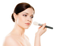 Portrait of a naked woman with makeup brushes Stock Image