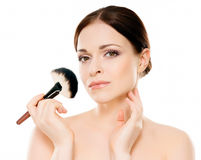 Portrait of a naked woman with makeup brushes Stock Photos