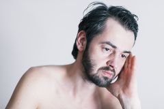 Young man with a problem. Portrait of a naked young man with a problem Royalty Free Stock Photography