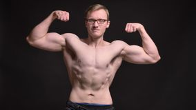 Portrait of naked young muscular man in glasses happily showinghis biceps into camera on black background. stock video