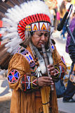 Portrait of a native american playing at a flute. Portrait of the radical American playing a flute dressed in national suit Royalty Free Stock Photo