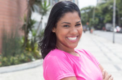 Portrait of a native latin woman in a pink shirt in city Stock Image