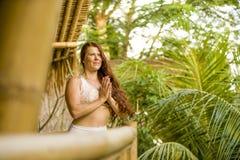 Portrait naturel de jeune femme heureuse et attirante avec de beaux longs cheveux rouges faisant l'exercice de m?ditation de yoga photographie stock