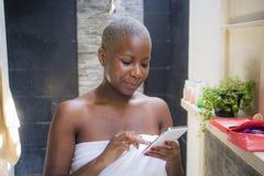 Portrait naturel de mode de vie de jeune femme afro-américaine d'intoxiqué heureux et attirant d'Internet dans la salle de bains  photos stock