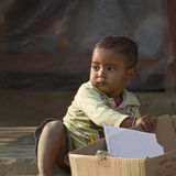 Portrait of a nepali kid playing with cardboard packaging Stock Image