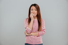 Portrait of a nervous asian girl biting her nails. While looking at camera isolated over gray background stock photos