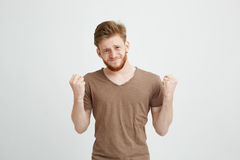 Portrait of nervous young handsome man hoping praying looking at camera over white background. Copy space Stock Photos