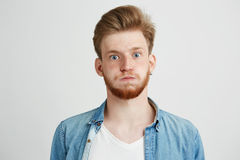 Portrait of nervous young man with beard looking at camera over white background. Copy space Royalty Free Stock Photography