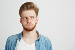 Portrait of nervous young man with beard wearing jean shirt looking in side over white background. Copy space Royalty Free Stock Image